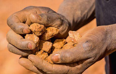 Goldwäscherinnen und -wäscher sieben kleinste Goldkörnchen aus dem Gestein