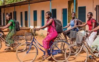 Mit dem Fahrrad fahren die Mädchen in die Schule.