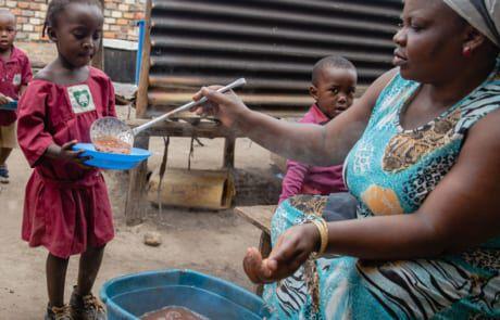 Frau teilt Essen an kleines Mädchen aus Uganda