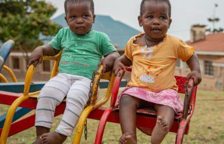Zwei Babys auf Karusell in Uganda