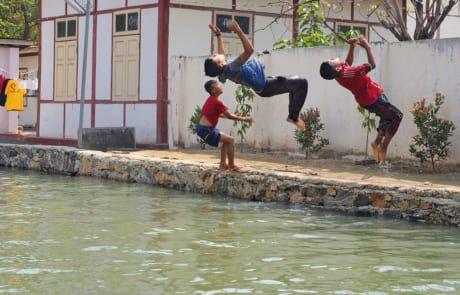 Kinder springen ins Wasser.