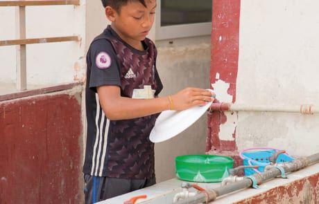 Ein Junge wäscht Geschirr.