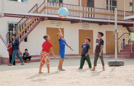 Kinder spielen mit einem Ball.