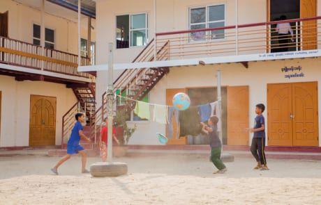 Vier Kinder spielen mit einem Ball im Hof des Jugendzentrums..