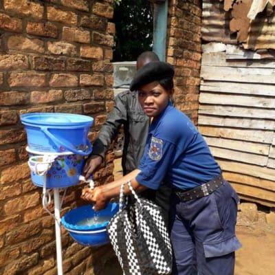 Polizistin wäscht sich die Hände bei einer Waschstation der Kirche.