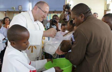 Pater Karl Wallner tauft Kinder in Tansania.