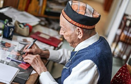 alter Mann beim Signieren