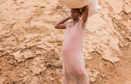 Eine schwangere Frau trrägt einen Sack auf dem Kopf.