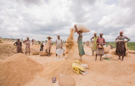 Frauen stehen auf einem Berg aus Reisresten
