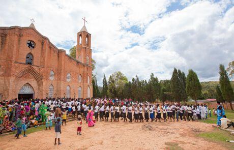 Tanzend und singend ziehen hunderte Menschen zum Gottesdienst in die Kirche ein.