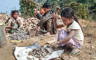 Kinder am Wegrand klopfen Steine für den Straßenbau.