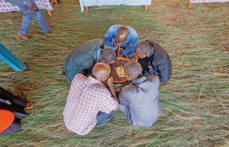 Männer trinken traditionelles Bier in Burundien