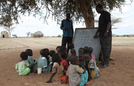 Lehrer und Kinder mit Tafel unter einem Baum