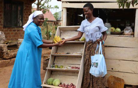 Eine Ordensfrau kauft Bananen bei einem Marktstand.