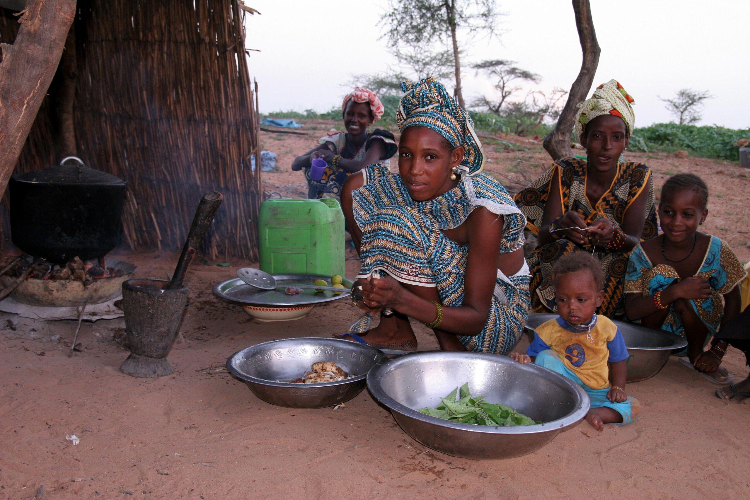 Frauen und Kinder kochen auf dem Boden