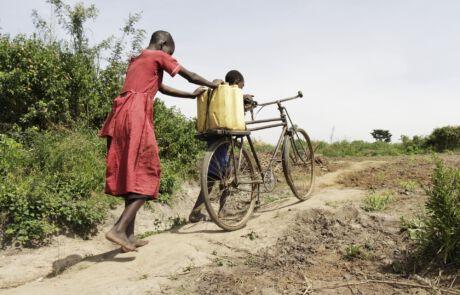 Zwei Kinder schieben Fahrrad mit Wasserkanister