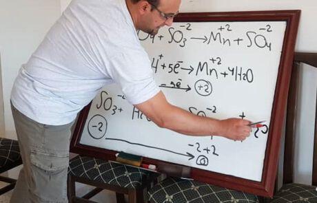 Mann schreibt auf behelfsmäßiger Tafel