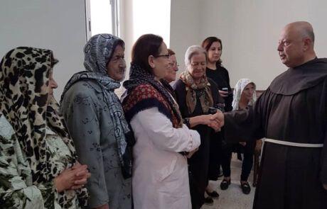 Bruder Hanna Jallouf reicht einer Frau die Hand.