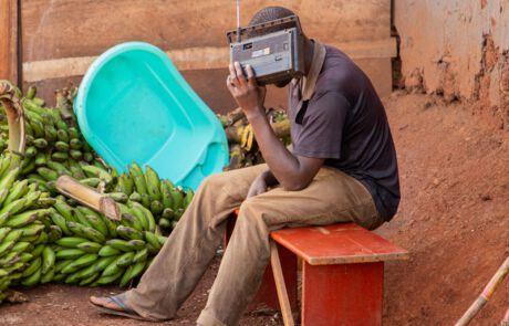 Mann hält sich Radiogerät ans Ohr.