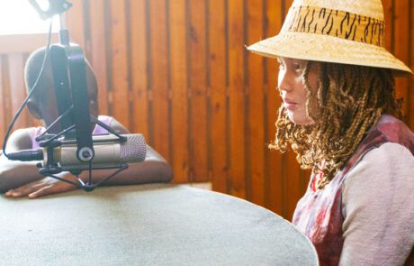 Mädchen mit Albinismus sitzt vor Mikrophon