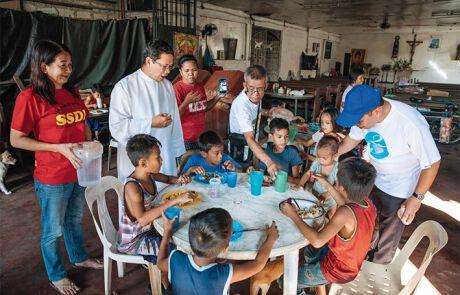 Kinder essen am Tisch neben Pfarrer Reynaldo Daguitera