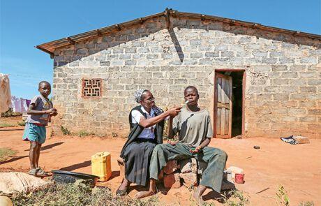 Frau hilft einem Jungen Zähne zu putzen