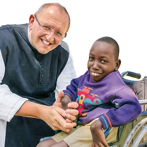Pater Karl Wallner und ein Junge im Rollstuhl