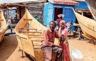 Ein Mann und eine Frau lehnen an einem unfertigen Boot.