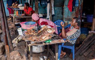 Frauen verkaufen gebratenen Fisch auf Holztischen