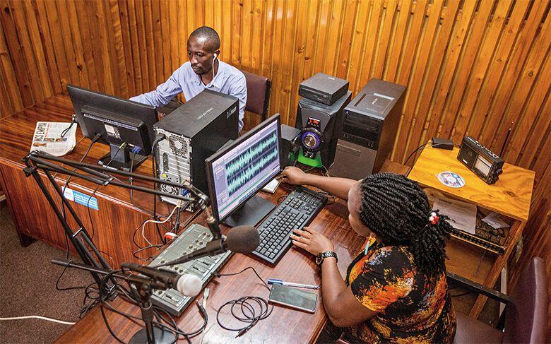 Gemeinsam mit einer Tontechnikerin bereitet ein Journalist seine Sendung vor.