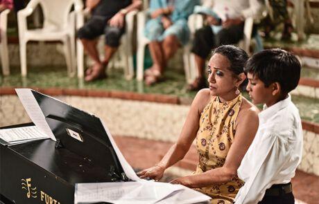 Marialena beim Klavierspielen mit einem Jungen
