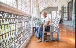 Vor einem der Schlafsäle für Männer sitzt Noel auf der Veranda