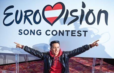 Vincent Bueno vor einem Eurovision Song Contest Banner