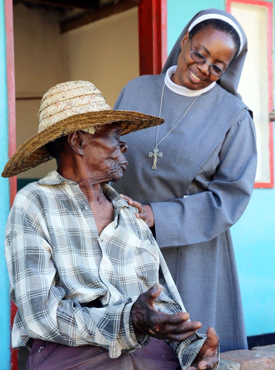 Ordensfrau spricht mit einem Leprapatient in Sambia