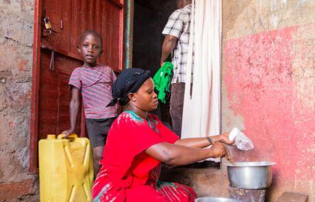 Frau sitzt am Boden und kocht, Kind steht daneben.