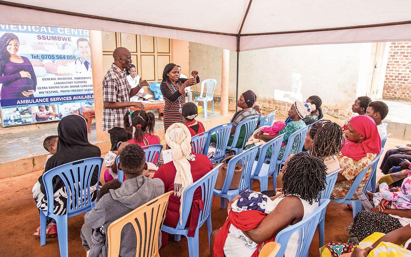 Rhodah und Opadde sprechen vor einer Gruppe Frauen