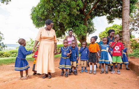 Direktorin Schwester Lucy mit Kindergartenkindern an der Hand.