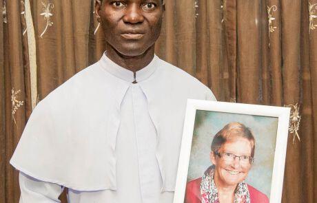 ein Priester mit einer eingerahmten Fotografie
