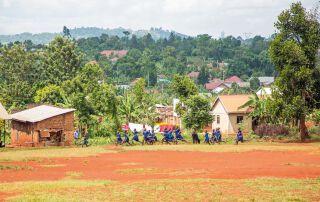 Auf einer Wiese vor der Schule laufen die Kinder im Turnunterricht um die Wette