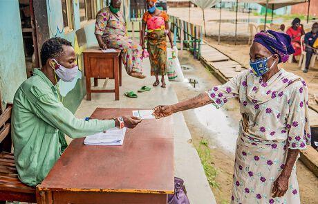 eine Frau übergibt einen Mann Papiere während der Corona-Pandemie