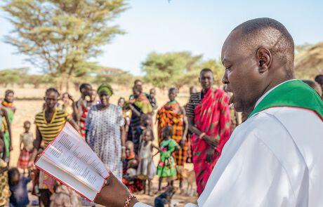 Priester liest aus der Bibel vor