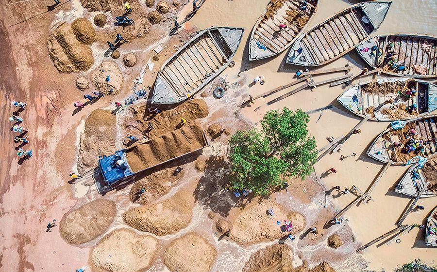 Voll beladene Boote mit Sand am Ufer des Niger-Flusses