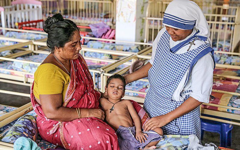 Teresa-Schwester und eine Helferin betreuen einen fieberkranken Jungen im Kinderhaus.